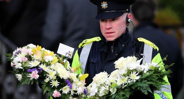 Flowers are brought to St Joseph's church in Dundalk for the State Funeral of Detective Garda Adrian Donohoe today. Picture: PA