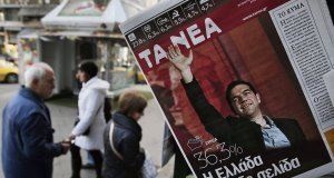 Athenians walks past a kiosk with newspapers featuring front page stories and photos of Alexis Tsipras, leader of Greece's Syriza party that won Sunday's national elections and has formed a coalition government.