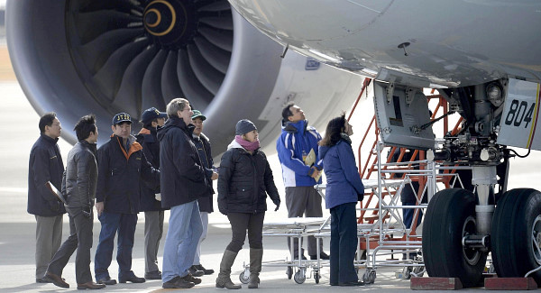 US officials, center, inspect a All Nippon Airways jet. Photo: AP / Kyoto News