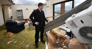 James Marriott surveys the damage in his roofless apartment after the Brisbane storm. Pic: AP