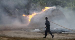 A firefighter runs towards a burning stack of hay which belongs to a Muslim household in Okkan, Burma. (AP Photo/Zin Chit Aung )