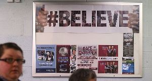 Fans walk by a #BELIEVE sign at Turf Moor today.