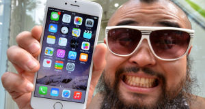'Mr Butch' celebrates after purchasing an iPhone 6 in Tokyo last week. Consumers have complained about glitches. Picture: Getty