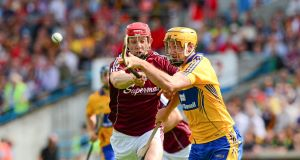 Cian Dillon, Clare, clears under pressue from Galway's Joe Canning. Picture: Ray McManus / SPORTSFILE