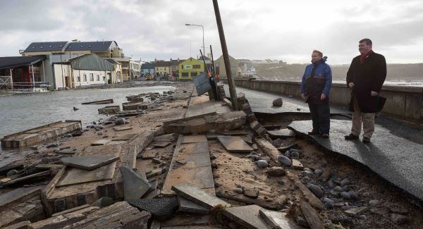 Local councillor Bill Slattery examines  the storm damage at the promenade in Lahinch, Co Clare, yesterday. Pic: Eamon Ward
