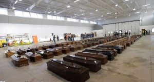 Coffins of migrants at Lampesuda Airport, Italy, October 5, 2013.