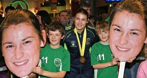 COOL HEADS: Katie Taylor is greeted by brothers Gearoid and Oisin Murphy from Greystones, Co Wicklow, following her arrival at Dublin Airport after winning her fifth world title. Picture: Colin Keegan