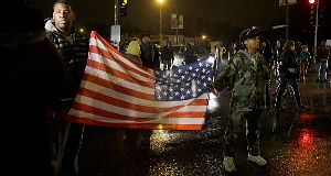 Protesters stand in the middle of a busy intersection blocking traffic last night.