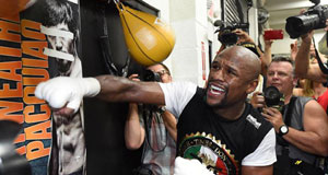 WBC/WBA welterweight champion Floyd Mayweather working on the speed bag in front of a poster of WBO welterweight champion Manny Pacquiao with his eyes and mouth taped over. Picture: Ethan Miller/Getty