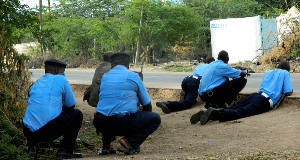 Kenyan police officers take cover outside the Garissa University College