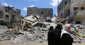 Palestinian women walk past a destroyed building in Gaza City in July. Picture: AP