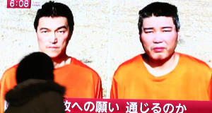 A passer-by watches a TV news program reporting two Japanese hostages, Kenji Goto, left, and Haruna Yukawa. Pic: AP