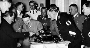 Hitler takes interest in a demonstration model of the Peoples Car, April 1938. Ferdinand Porsche is to the left with the moustache.
