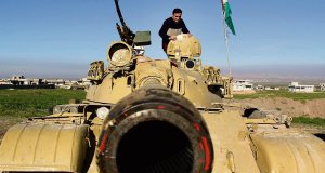 A Kurdish peshmerga militaman stands on a tank preparing for battle against the Islamic State group in northern Iraq. Picture: AP/Kurdistan Region Security Council