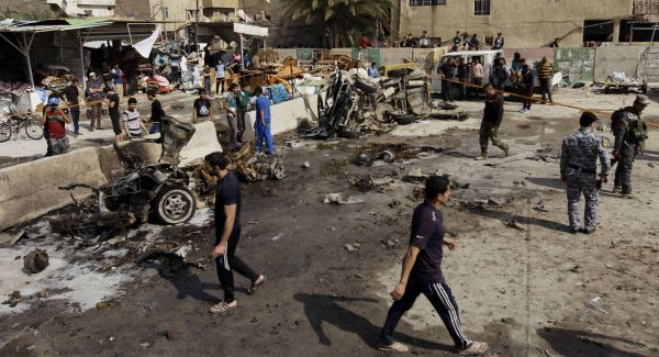 Iraqis inspect the scene of a car bomb attack in the Ameen neighborhood in eastern Baghdad