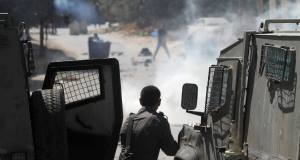 An Israeli soldier aims his weapon at a Palestinian during clashes in Hawara, West Bank today. Picture: AP