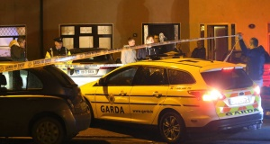 Gardaí and onlookers at the scene of the shooting in Clondalkin tonight. Picture: PA