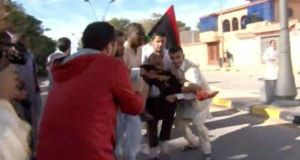 This image made from video shows an injured protester being carried away. Picture: AP