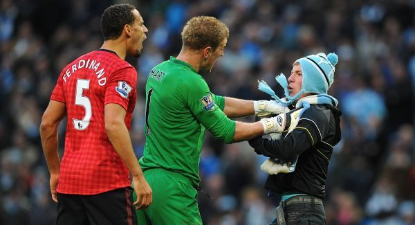 Manchester City goalkeeper Joe Hart holding back Matthew Stott as he goes towards Manchester United's Rio Ferdinand.Picture: PA