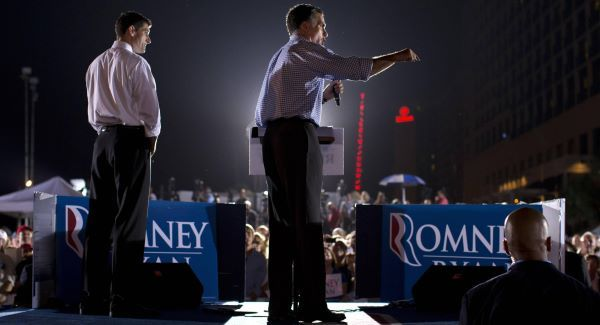 Mitt Romney speaks as vice presidential running mate Paul Ryan looks on during a campaign rally in Florida yesterday. Picture: AP
