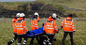 Members of the Doolin unit of the Irish Coast Guard transporting the injured woman to the visitor centre at the Cliffs of Moher. Pic: Press 22