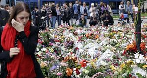Mourners gather near to the massive field of flowers in front of the Oslo Cathedral in Oslo, Norway, today. Pic: AP