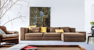 A stark contemporary room is softened by the warm Xsmall sofa (LOMI €2,975), while the eye is drawn downwards from the double height ceiling by a prominent canvas and tree branches with a sculptural aesthetic.