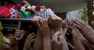 Palestinians carry the body of Mohammed al-Araj during his funeral after he was shot during clashes with Israeli troops. Pic: AP