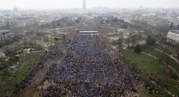 "Overhead view from the Eiffel Tower of thousands of people gathering to protest on the ""Champs de Mars"""