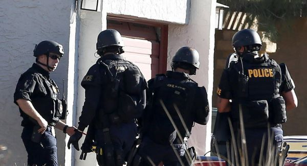 A SWAT team prepare to enter the home of a suspected gunman.