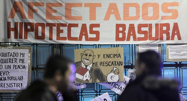 "People walk by a banner reading ""Rubbish mortgage"" and a drawing of a banker reading ""They even rescued me"" during a protest against evictions outside Bankia's headquarter in Madrid, today. Pic: AP"