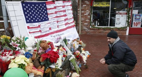 A mourner pays his respects near a US flag showing the names of victims at a makeshift memorial in the Sandy Hook village of Newtown. Picture: AP