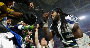 Cornerback Richard Sherman #25 of the Seattle Seahawks celebrates with fans after defeating the Arizona Cardinals 35-6 in the NFL game at the University of Phoenix Stadium on December 21, 2014 in Glendale, Arizona.