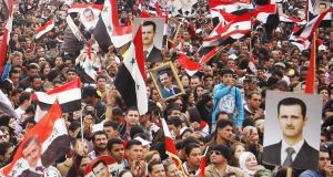 Pro-regime protesters chant slogans during a rally at Umayyad Square in Damascus, Syria today.