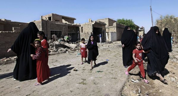 Iraqi women and children walk near the scene of a car bomb attack in the town of Taji today. Picture: AP