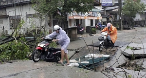 Tourists make their way on a damaged road on Koh Samui island after heavy storms and rain hit the southern part of the country in Surat Thani province.