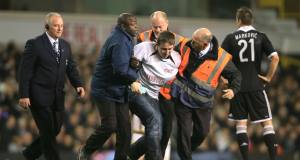 A pitch invader is escorted off the pitch by security during the match at White Hart Lane. Picture: PA