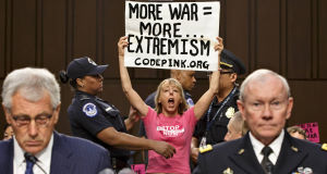 Anti-war activists interrupt a Senate Armed Services Committee hearing with Defense Secretary Chuck Hagel, left, and Army Gen. Martin Dempsey