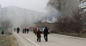 Residents pass by burning houses, a dead body in the background, in Mariupol, after a crowded open-air market in Ukraine's strategically important coastal city of Mariupol came under rocket fire.