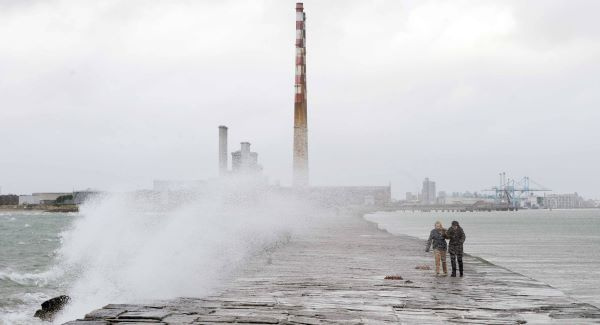 People brave the elements and ignore the weather warning to stay away from exposed coastal areas, as they walk out to Poolbeg lighthouse in Dublin this afternoon. Picture: Laura Hutton, Photocall