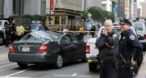 A pair of San Francisco police officers look over the scene where a window washer fell 11 stories onto a moving car. Picture: AP