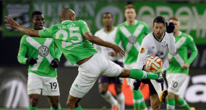 Wolfsburg's Naldo, left, and Everton's Kevin Mirallas, challenge for the ball. Picture: AP