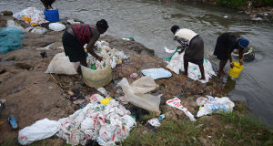 A group of women wash used plastic bags for re-use at the shores of the river in Nairobi.